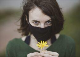 Vrouw met mondmasker en bloem